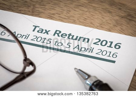 UK Income tax return form for 2016 on a desk with pen and glasses
