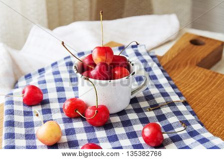 Composition of cup and berries. Cherries is the reason of the longevity . White retro cup and berries on a checkered napkin on the table. Retro cup and berries on a wooden cutting board