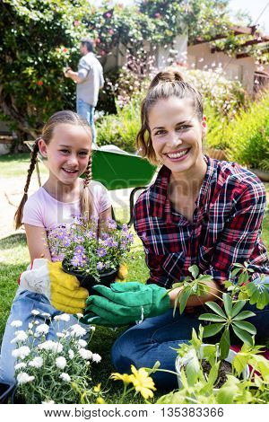Smiling mother and daughter gardening together in garden on a sunny day
