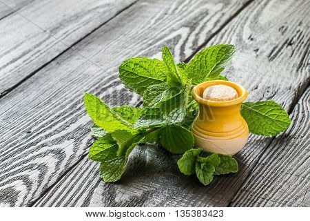 Mint essential oil in a small yellow clay jar and fresh mint on a dark wooden table