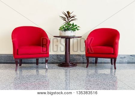 Modern red armchairs and table in a foyer