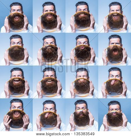 set of emotions. young emotional bearded man with different facial expressions behind big round magnifying glass in hands as emoticon