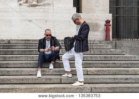 MILAN ITALY - JUNE 19: Two fashionable men wait outside Ferragamo fashion show building during Milan Men's Fashion Week on JUNE 19 2016 in Milan.