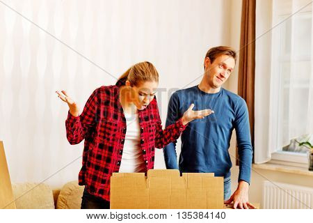 Couple unpaking boxes, stressed woman looking to inside