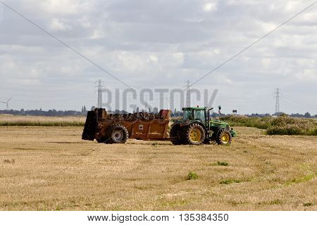 MARCH, UK - SEPTEMBER 25: A tractor begins to muck spread onto a recently harvested field of wheat on September 25, 2015 in March. In 2015 the UK agricultural industry produced over 16Mn tons of wheat