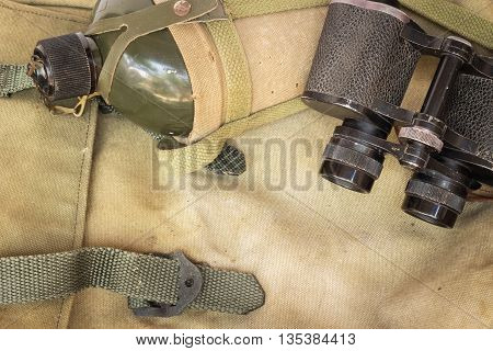 Soldier flask (canteen) in decay cloth winding and classic binoculars on rucksack