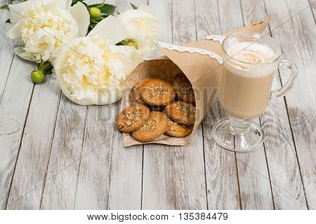 Glass of cappuccino next to cookies and pionies flowers on the white wooden background. Place for text.