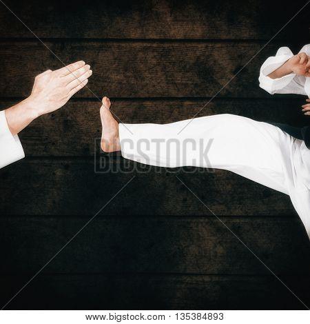 Female athlete practicing judo against dark fence