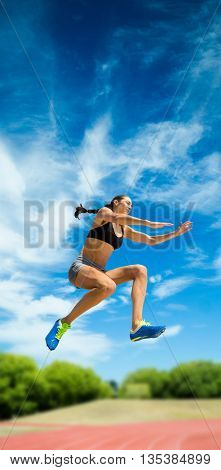 Sporty woman jumping against athletics field on a sunny day