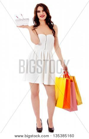 Young woman holding small empty shopping basket and shopping bags