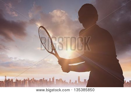 Female athlete playing tennis against city on the horizon