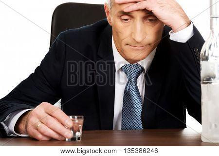 Overworked man drinking vodka in office
