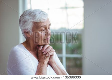 Senior woman with eyes closed praying at home