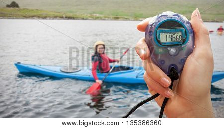 Composite image of a hand holding a timer against smiling woman in a kayak