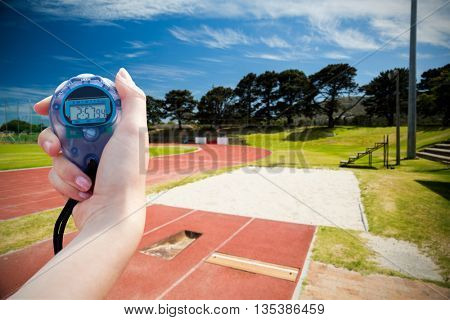 Composite image of a woman holding a chronometer to measure performance against high angle view of track