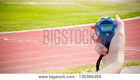 Close-up of a woman holding a chronometer to measure performance against race track on a sunny day