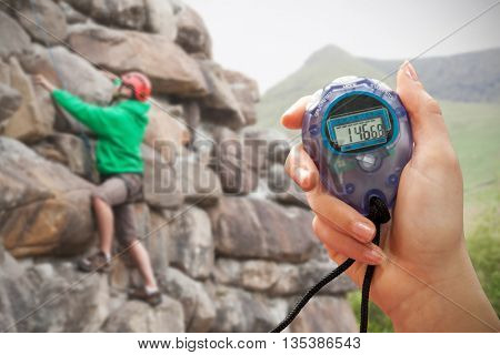 Composite image of a hand holding a timer against focused man climbing a large rock face