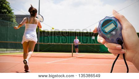 Close up of woman is holding a stopwatch against tennis match in progress on the court