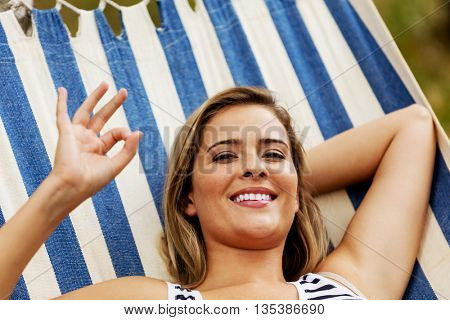 Young blonde woman resting on hammock and gesturing perfect