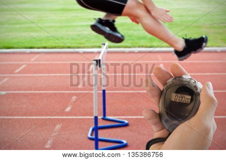 Composite image of coach is holding a stopwatch against selfassured male athlete jumping above hedge during a race