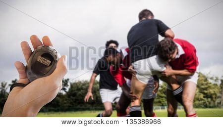 Composite image of coach is holding a stopwatch against rugby players tackling during game