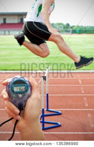 Close up of a hand holding a timer on a white background against determined male athlete jumping above hedge during a race