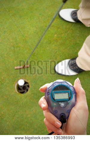 Close up of woman is holding a stopwatch on a white background against golfer putting golf ball in the hole