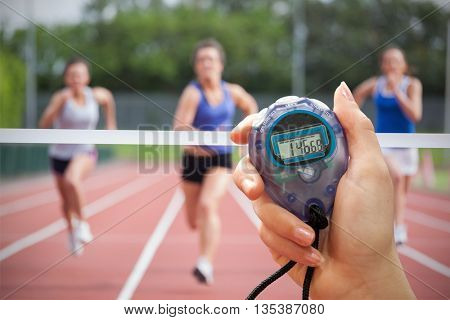 Composite image of a hand holding a timer against athletes racing towards finish line