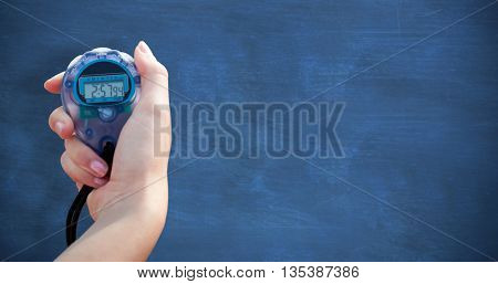 Close-up of a woman holding a chronometer to measure performance against blue chalkboard