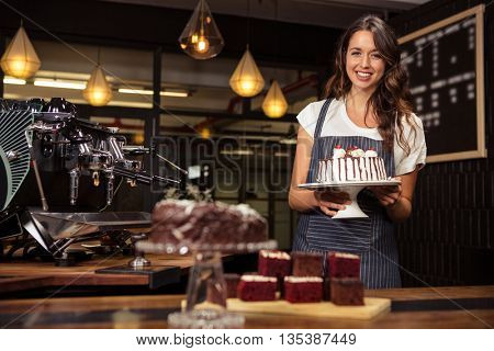 Smiling barista holding plate with cake at coffee shop