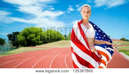 Portrait of sporty woman holding American flag against athletics field on a sunny day