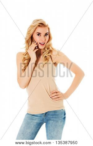 Shocked young woman talking through a smartphone