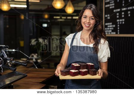 Smiling barista holding plate with cakes at coffee shop