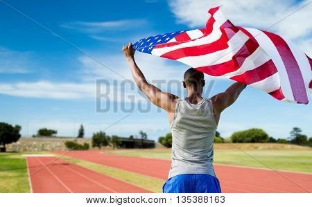 Rear view of athletic man holding the American flag against athletics field on a sunny day