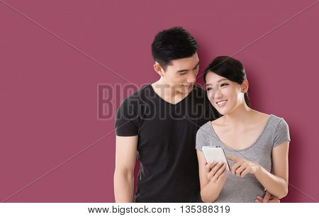 young Asian couple shopping and looking at cellphone against colorful background