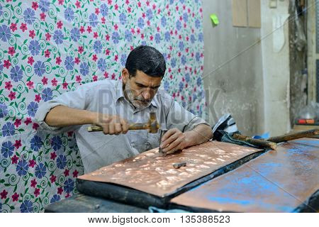 ISFAHAN - APRIL 19: Unknown man making traditional iranian souvenirs in a market (Isfahan Bazaar) in Isfahan Iran on April 19 2015. Bazaar is the most important tourist attraction in Isfahan Iran.