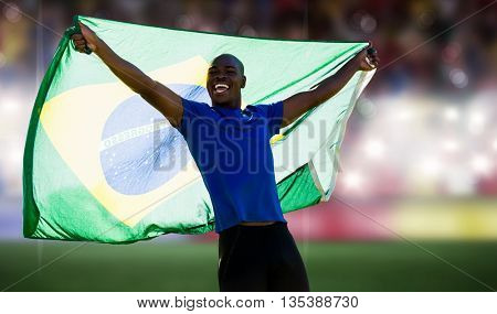 Front view of Brazilian sportsman is smiling and raising a flag against sports arena