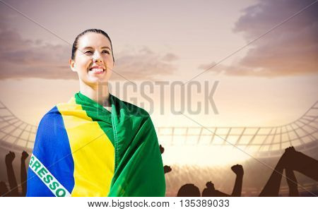 Sporty woman holding Brazilian flag against football stadium with cheering crowd