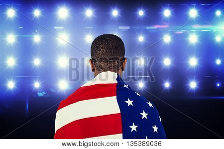 Athlete with american flag wrapped around his body against composite image of blue spotlight