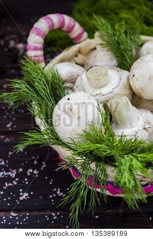 fresh mushrooms with dill and tomatoes on dark wooden background