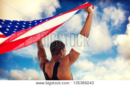 Athlete holding american flag against scenic view of blue sky