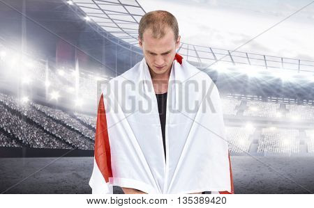 Athlete with england flag wrapped around his body against sports arena