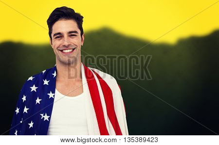 Athlete with american flag wrapped around his body against blurred mountains