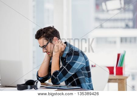 Stressed young man sitting at his desk in the office