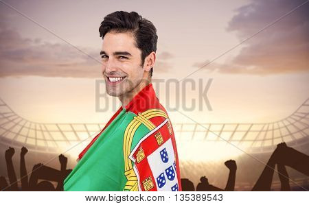 Athlete with portugal flag wrapped around his body against football stadium with cheering crowd
