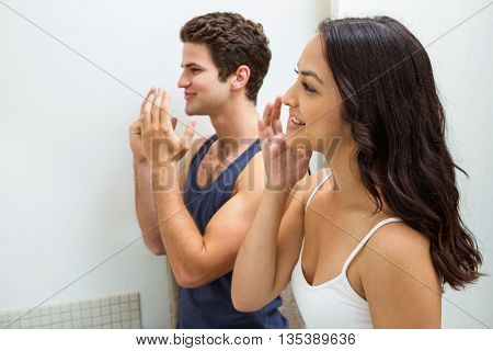 Young couple applying cream on face while looking in mirror at bathroom