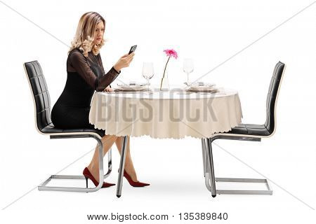 Young woman reading a text message seated at a restaurant table isolated on white background