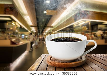 Hot black coffee in white cup on the wood table at food court background