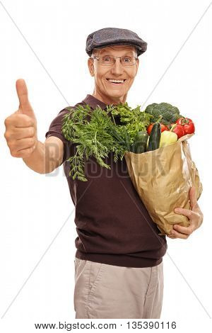 Vertical shot of a satisfied senior holding a grocery bag and giving thumb up isolated on white background