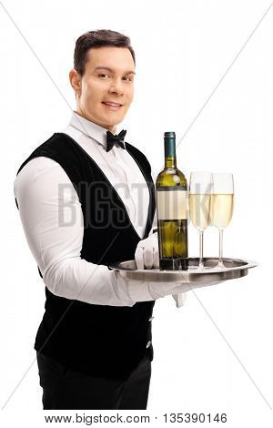 Vertical shot of a cheerful waiter holding a tray with a bottle of wine and two glasses isolated on white background